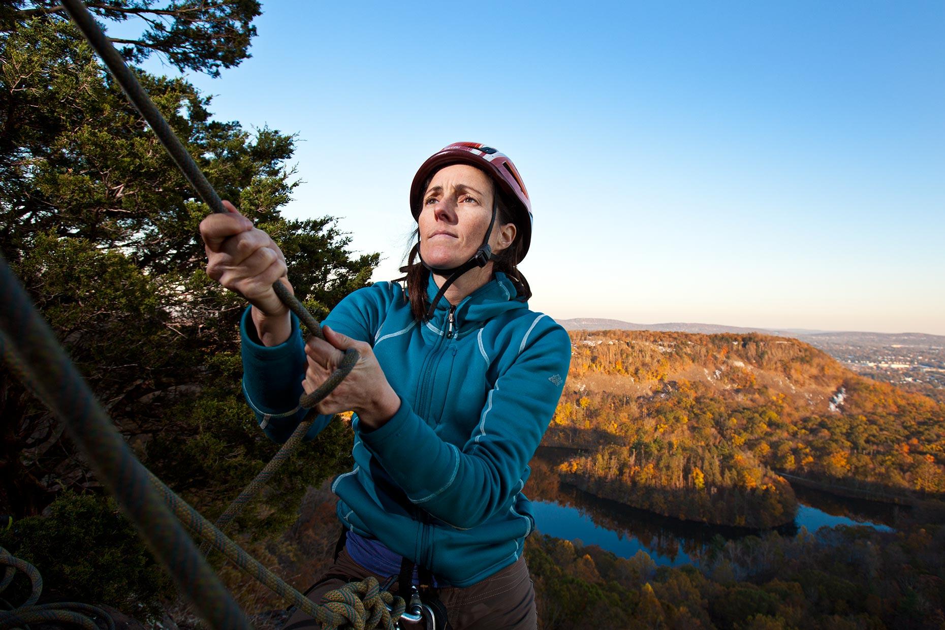 A middle aged woman pulls on a rope on top of a Connecticut cliff in winter