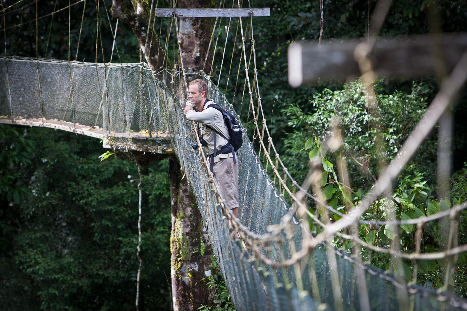 A young adventure tourist pauses on a swinign bridge to admire the view in Borneo