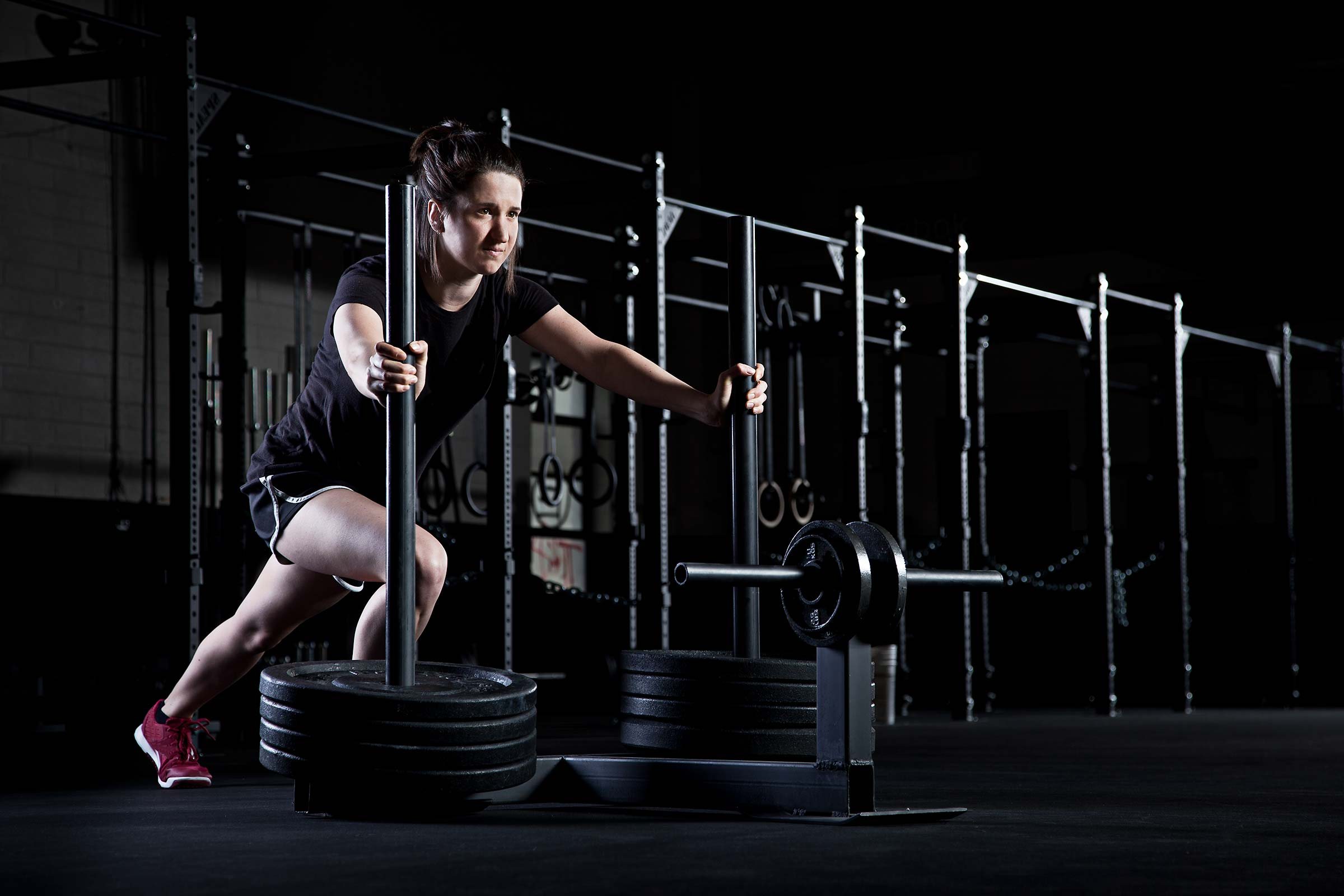 an action shot of a young woman pushing a weight sled in a Connecticut gym