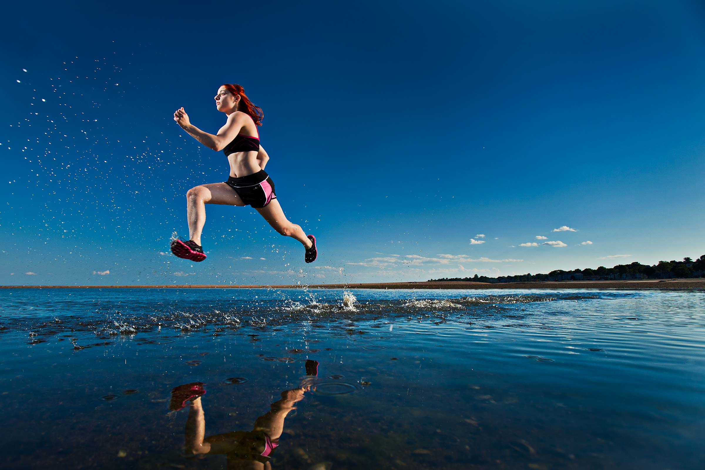 a young female runner kicks up a spray of water while running on a Connecticut beach