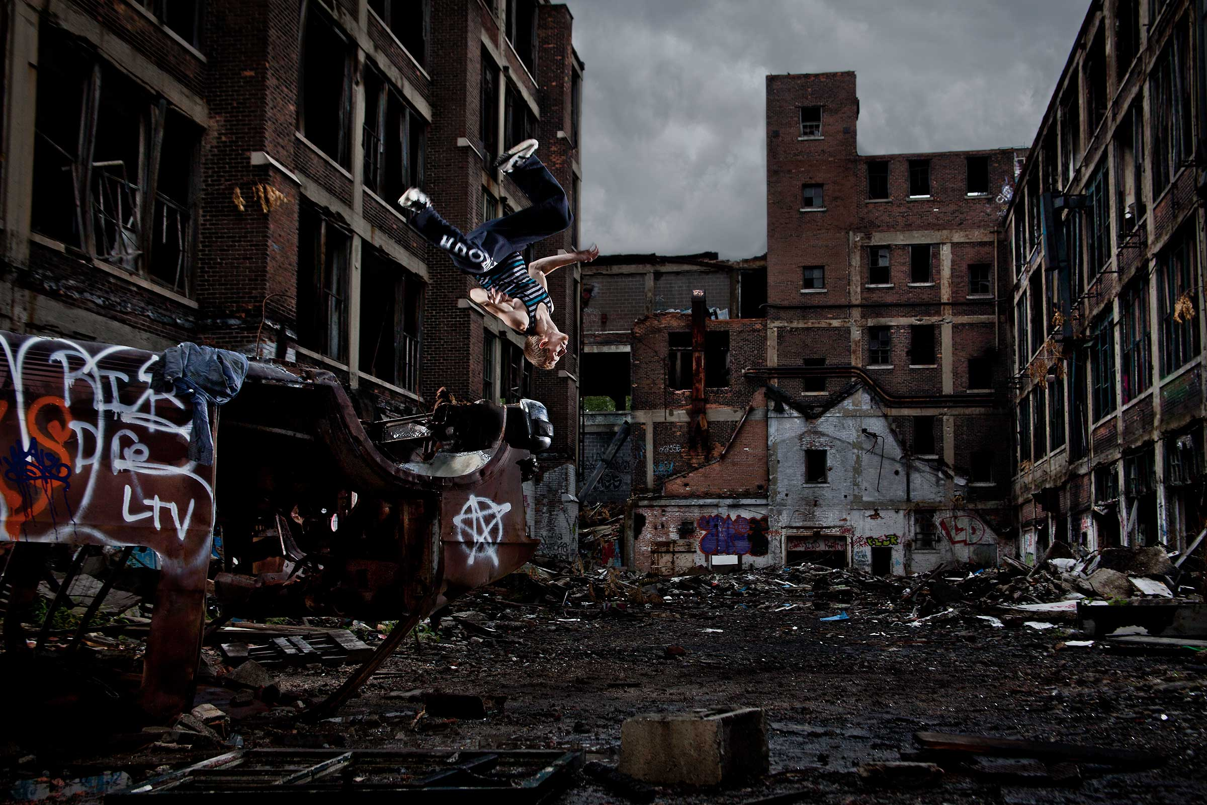 a young male parkour athelete does a flip off an abandoned car in an industrial location