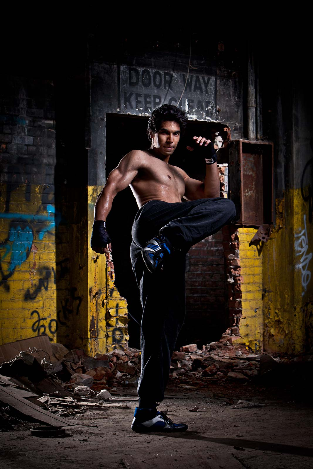 A shirtless muscular Indian man praciticing martial arts in an industrial setting