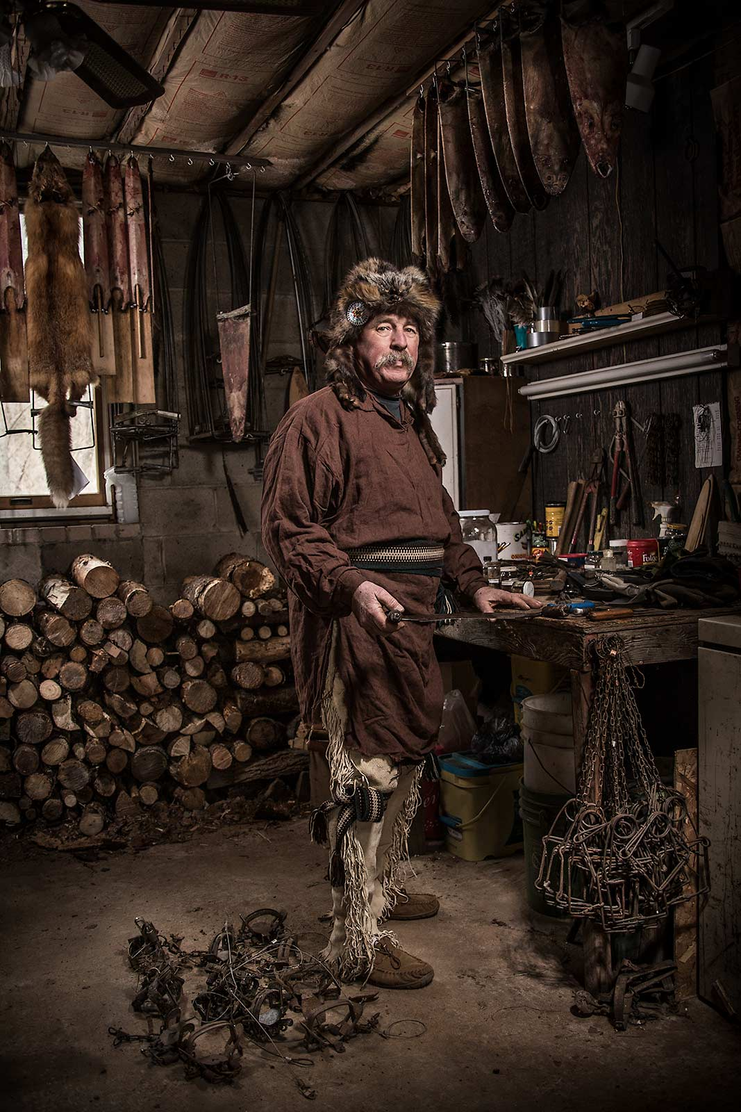 A older man dressed in tradional trapper clothing in workshop in New Jersey