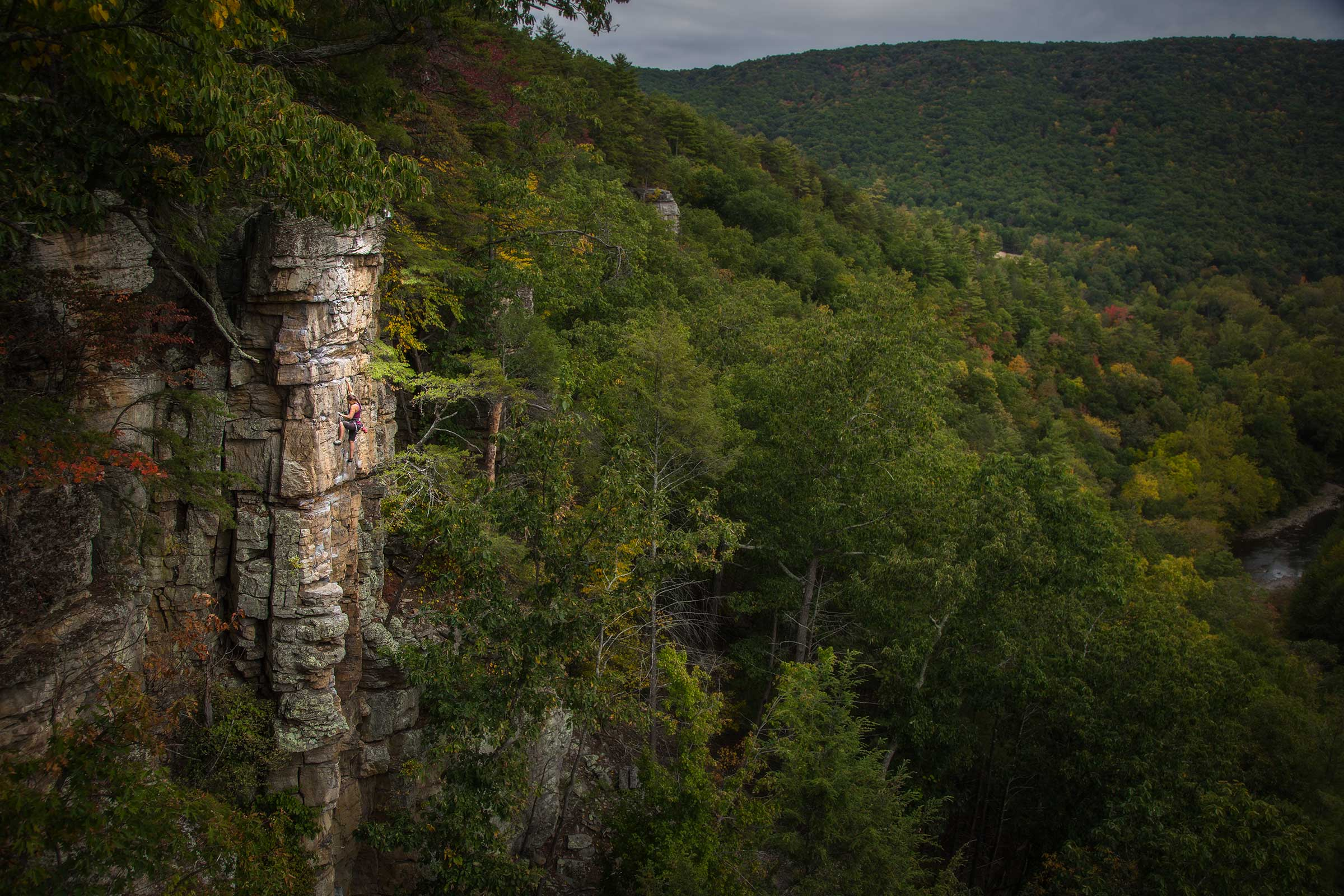 A panoramic view of a female rock climber with dramatic light in mountains in West Virgina