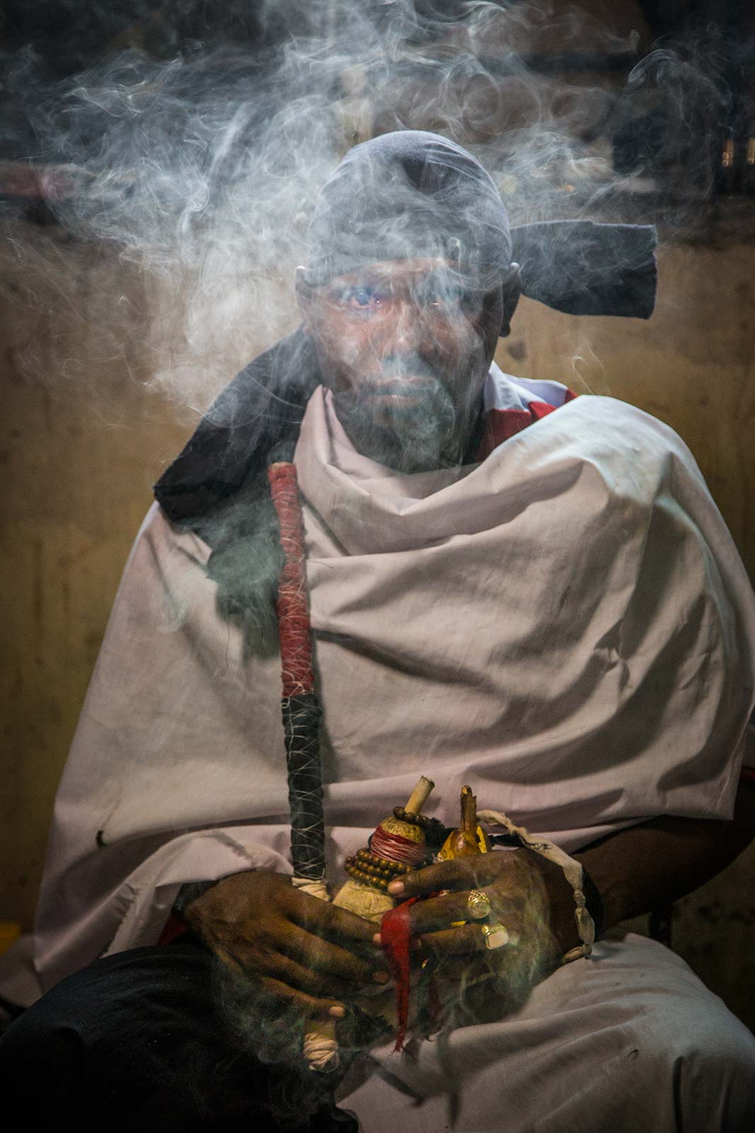 A smoky moody portrait of a  Tanzanian witch doctor performing a ritual